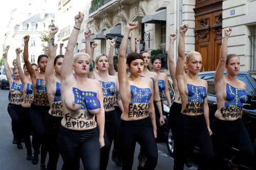 Topless activists of the Ukrainian women movement Femen raise their fists during a